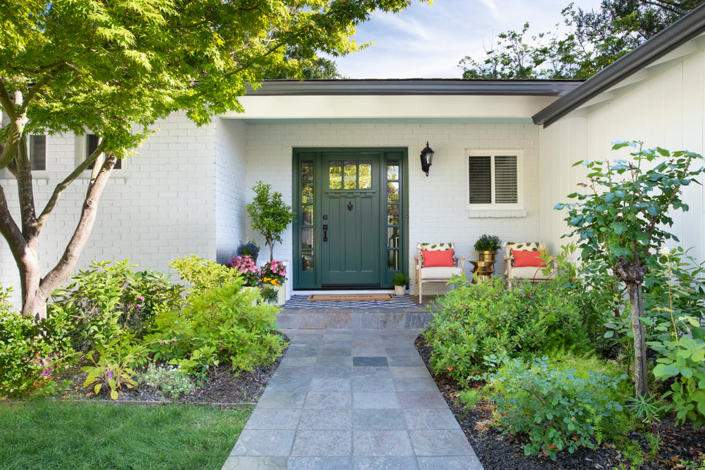 Charming, landscaped home exterior with painted white brick, black trim paint and a dark green front door.