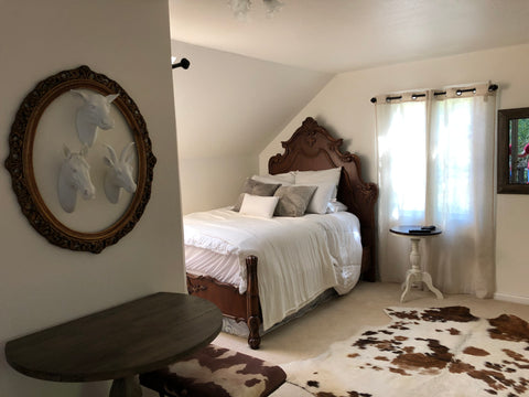Country cottage guest room with Swiss Coffee white walls and vintage headboard
