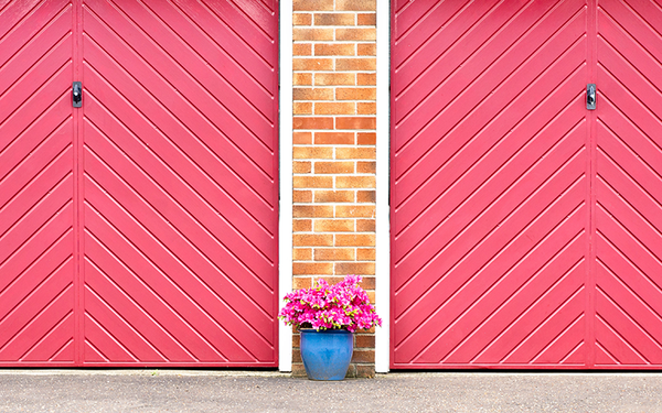 chevron style garage door with bright pink paint and brick siding featured by Kelly-Moore Paints
