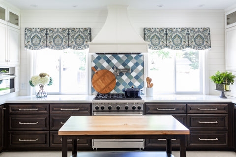 Wendy Glaister used Kelly-Moore 23 Swiss Coffee for this kitchen with dark brown stain cabinets, blue backsplash tiles and scalloped blue curtains