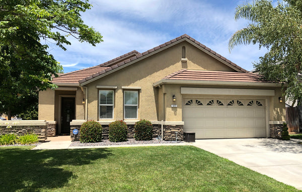 BEFORE bland yellow stucco house gets a warm gray brown neutral exterior paint makeover with popular pink orange front door.