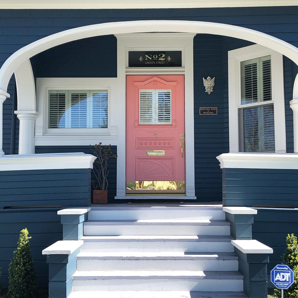 Colonial Vicotorian Queen Anne style home with a bright exterior color palette of blue exterior walls, white trim and archways with a pink front door.