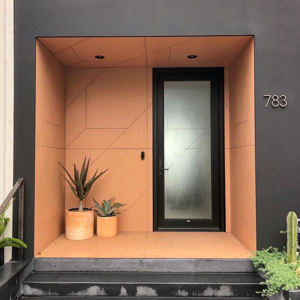 Modern house exterior with unique inset entrance. The geographic tile pattern is complemented by a terracotta and black paint color palette.