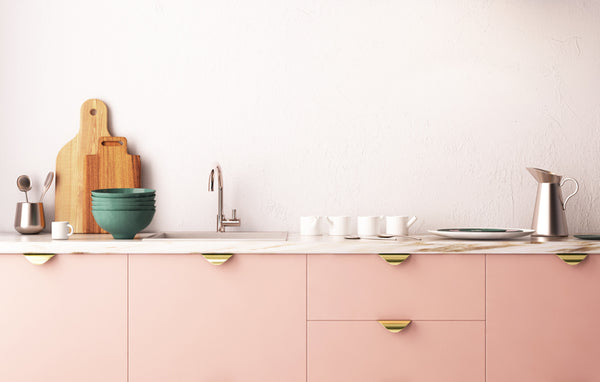 Kelly-Moore features pink cabinets to show modern design with brass tab pulls and rustic cutting board accessories