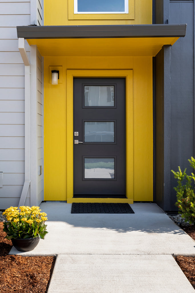 Townhouse exterior with a bright and crisp yellow and black color blocking palette with modern entry