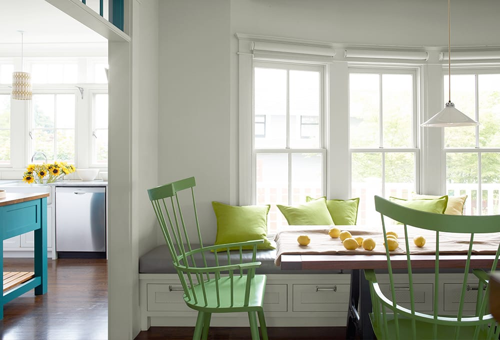 Dining room painted white, with large windows with white painted trim and bright green painted chairs.