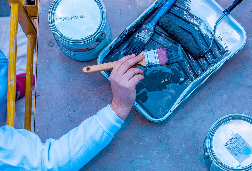 A contractor holding a paint brush after dipping in a paint tray with two gallons Benjamin Moore of paint.