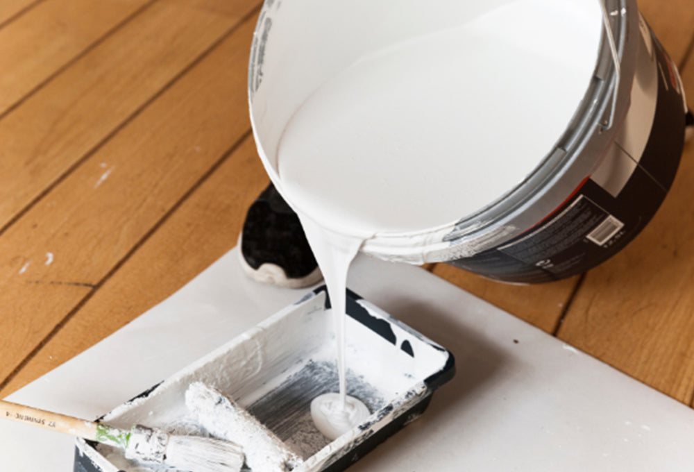 A 5 gallon pail of primer being poured into a paint tray with a paint roller and paint brush.