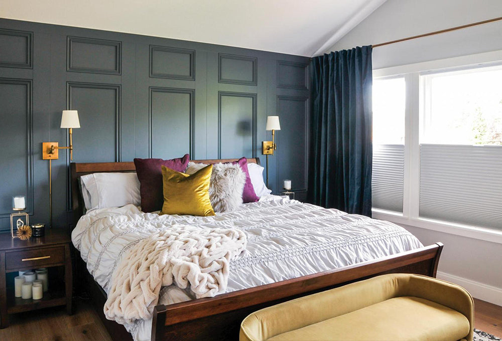 A bedroom with a dark accent wall, with a wood bed and gold and purple pillows with a white duvet.