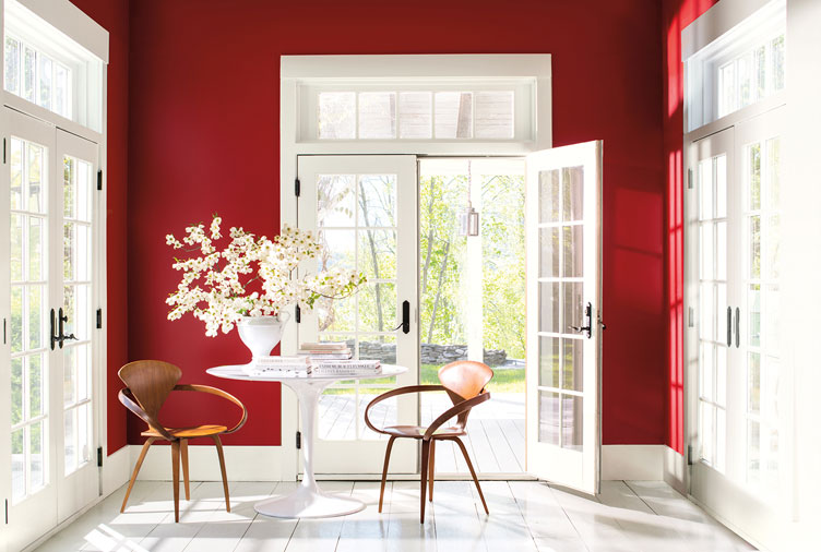 A room with a bright red accent wall, large windows and doors with white painted trim.