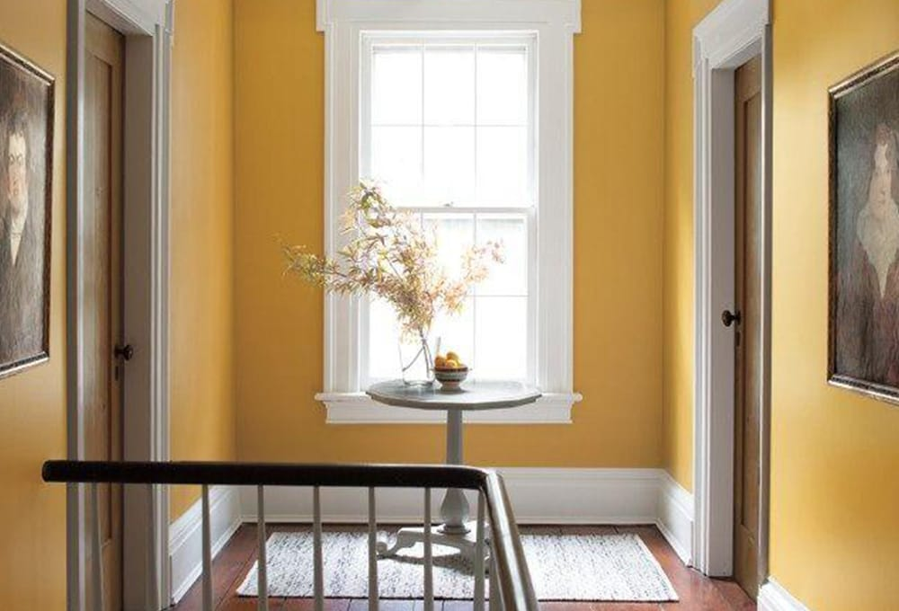 A hallway painted with a golden yellow, and a large window with white trim.