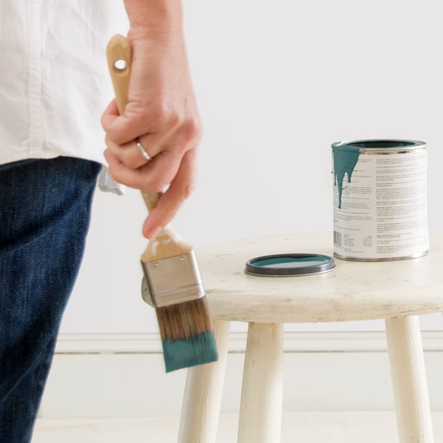 A woman's hand holding a paint brush with green paint on it, with an open Benjamin Moore paint color sample pint on the table next to her.