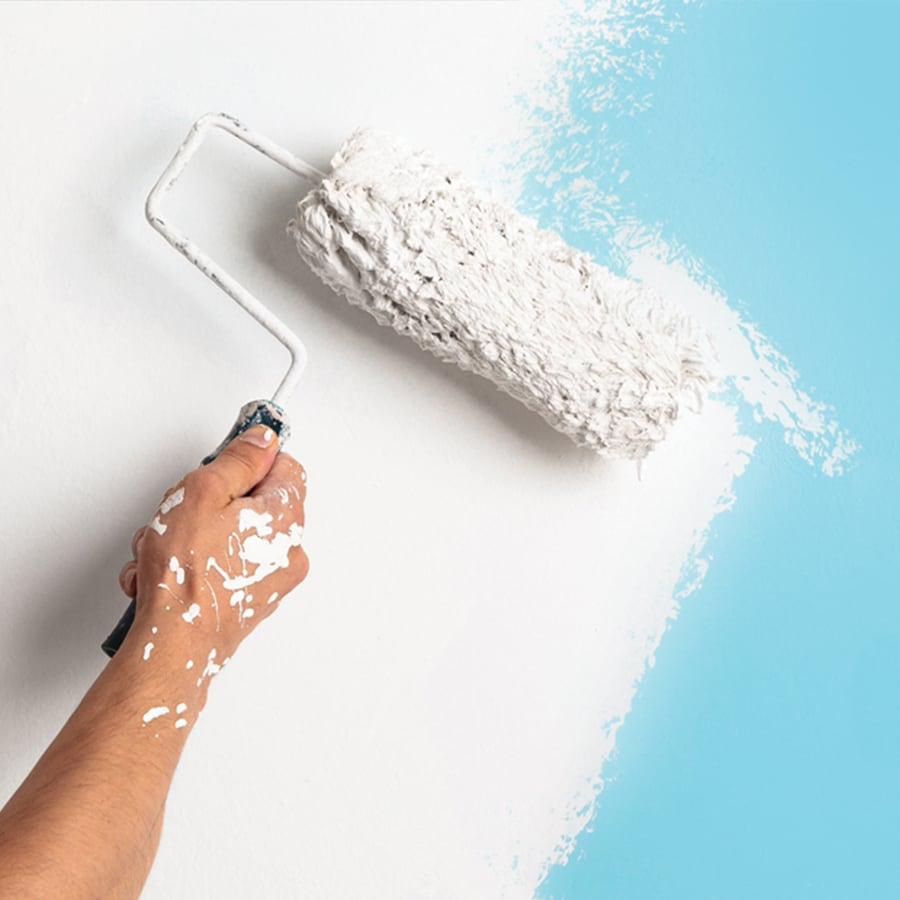 A person's hand with a paint roller, rolling white paint onto a light blue wall.