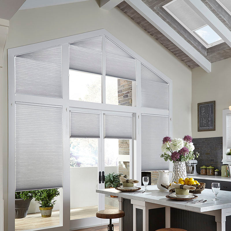 kitchen with beige walls and white window trim, wall of large windows of odd shapes and sized covered with customizable window treatments from Regal Paint Centers, designed for energy efficiency