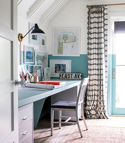 A home office painted with light blue and blue and white furniture.