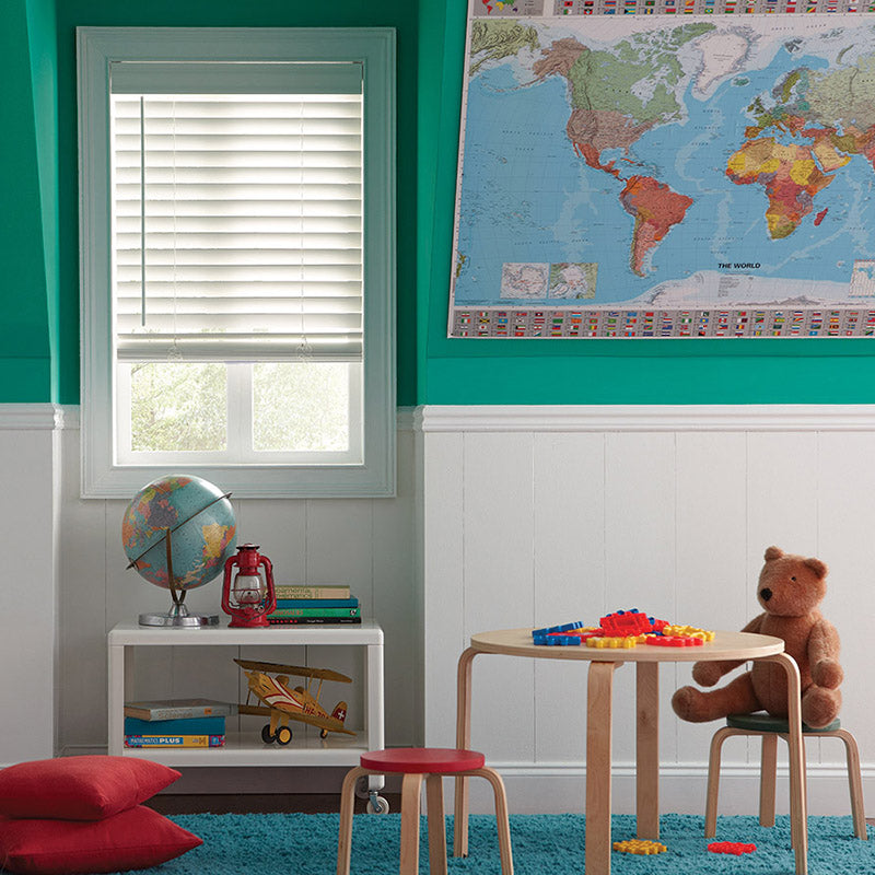 kids playroom with aqua green walls and white wainscoting, window with child and pet safe window blind.
