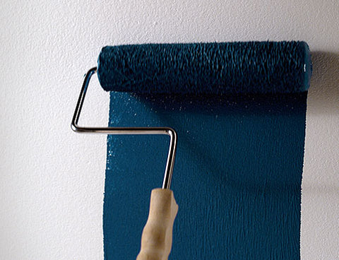 A paint roller painting dark blue on a white wall.
