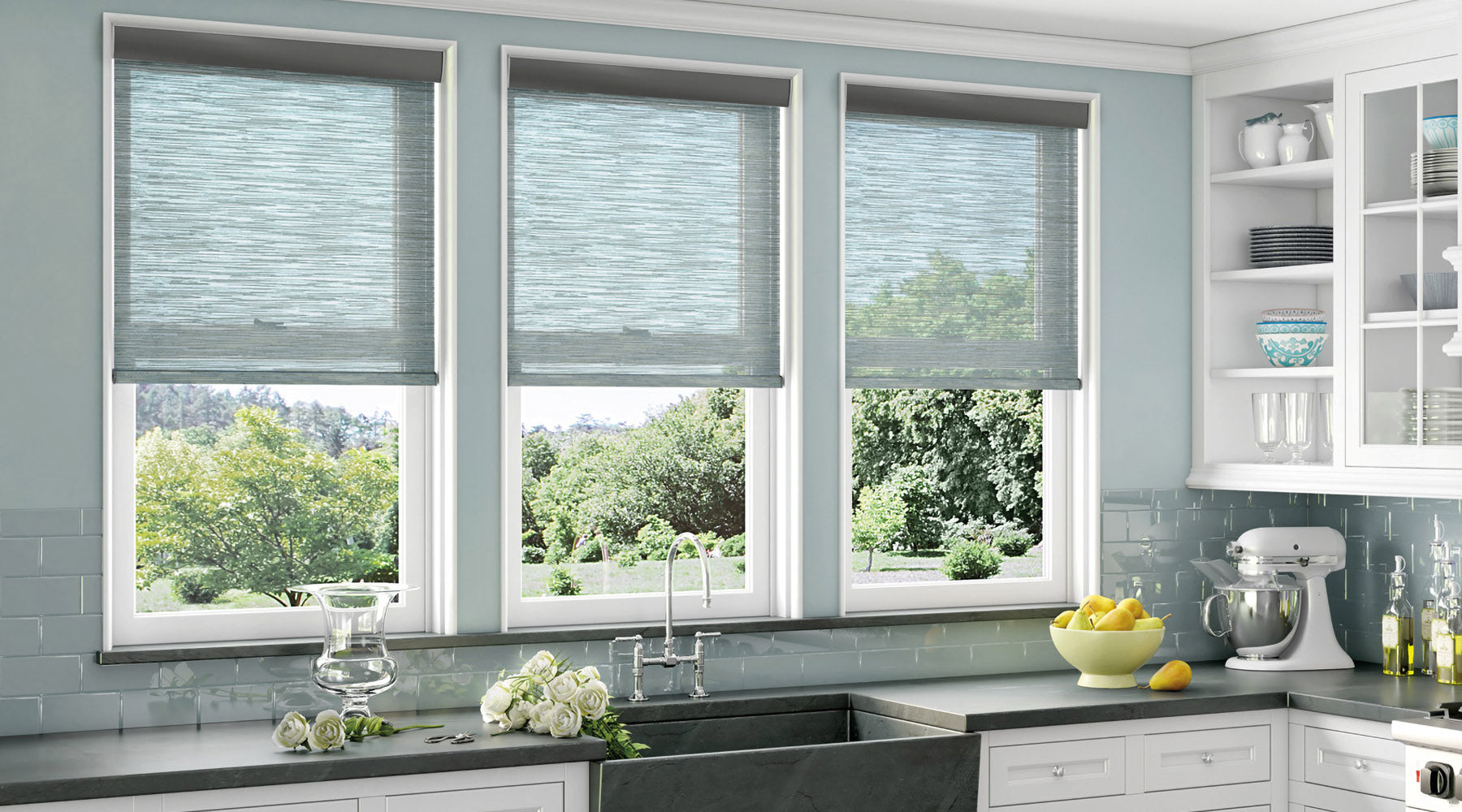 shop custom window treatments at Regal Paint Cetners. Modern kitchen with gray/blue walls, white cabinets, and modern light filter window shades.