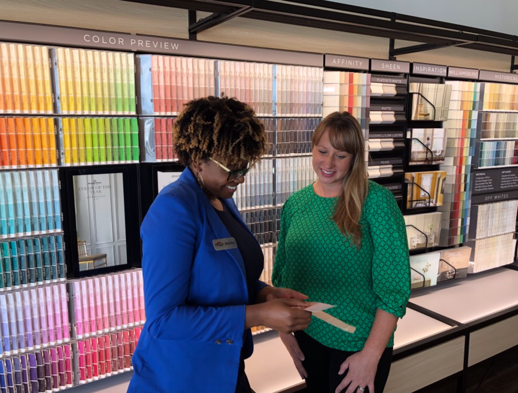 A color consultant a Regal Paint Centers in Annapolis, MD helping a customer choose a paint color, while looking at paint color chips.