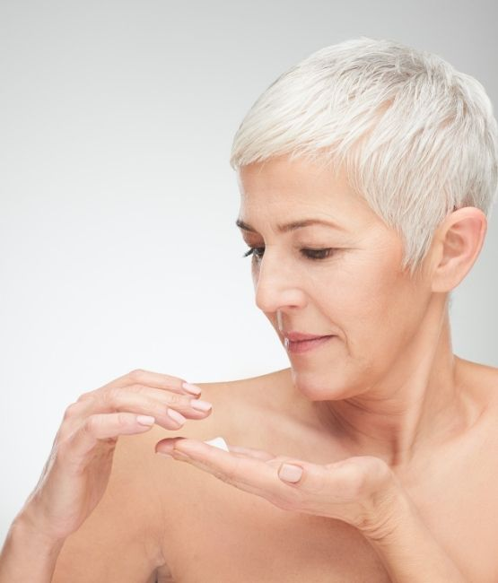 Mature woman treating her dry skin with CameLife Nourishing Body Mousse
