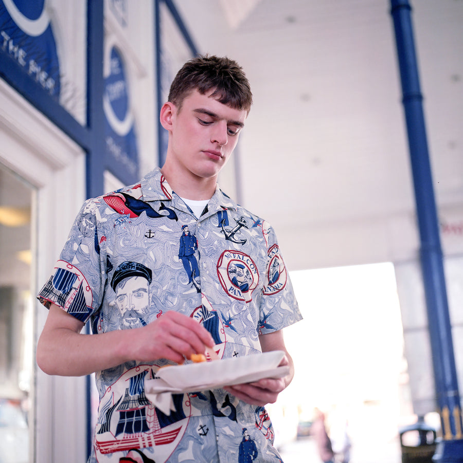 A man eating fish and chips in a Gitman Vintage Shirt
