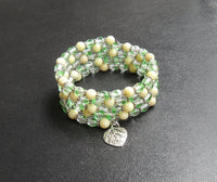 memory wire wrap bracelet - chartreuse serpentine and Czech firepolished bead with lead-free silver leaf charm - has matching earrings