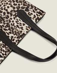 LEATHER HANDLE SHOT OF THE TAB TOTE IN SNOW LEOPARD