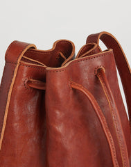 Handle shot of Mini Hammered Stud Bucket Bag in Saddle