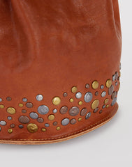 Stud Detail shot of Mini Hammered Stud Bucket Bag in Saddle