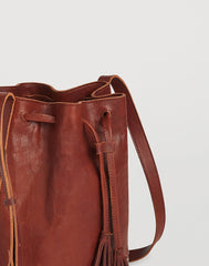 Detail of pull on Hammered Stud Bucket Bag in Cognac