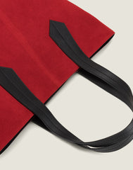 LEATHER HANDLE SHOT OF THE TAB TOTE IN RED SUEDE