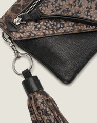 DETAIL SHOT OF THE TASSEL KEYCHAIN IN CHEETAH ON THE WEARABLE WALLET IN CHEETAH