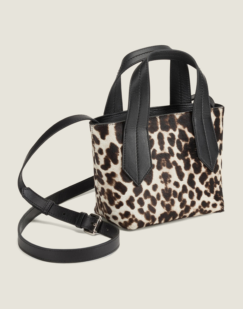SIDE SHOT OF THE TAB TOTE MINI IN SNOW LEOPARD AND LEATHER CROSSBODY STRAP