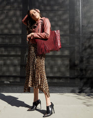 Model wearing Cascade Fringe Tote in Burgundy