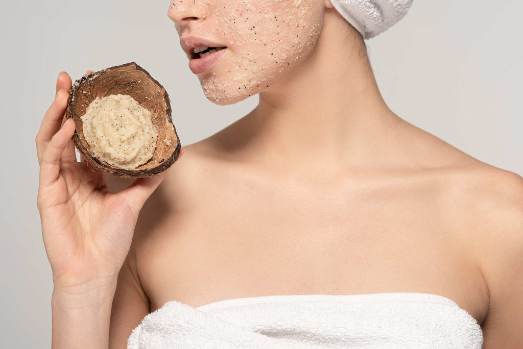 Woman exfoliating skin with natural coconut scrub