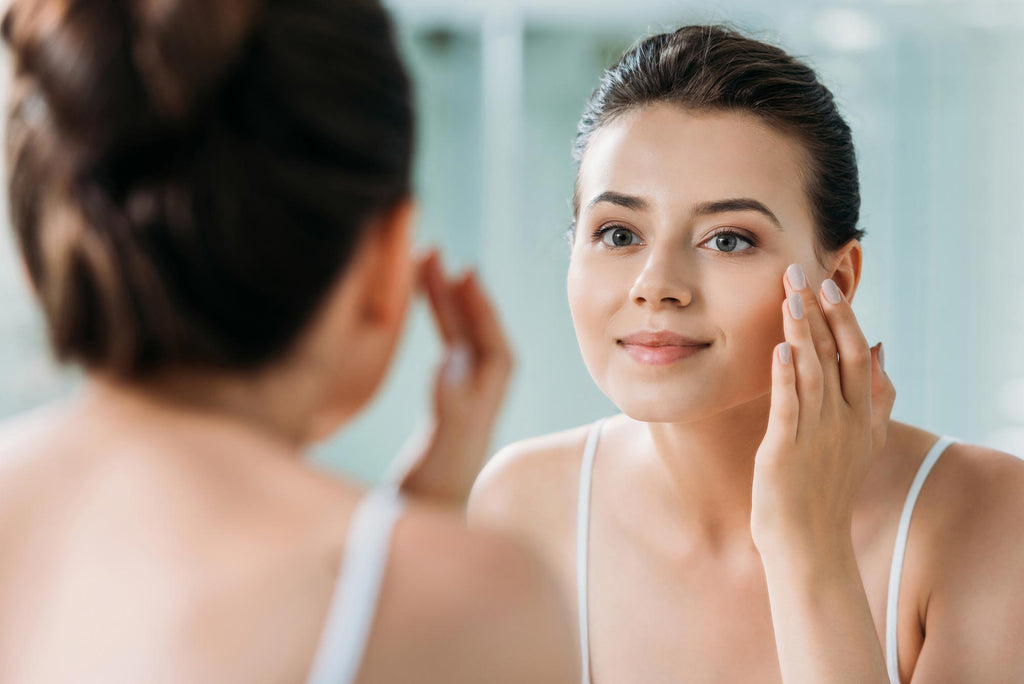 Woman smiling and applying skincare in mirror