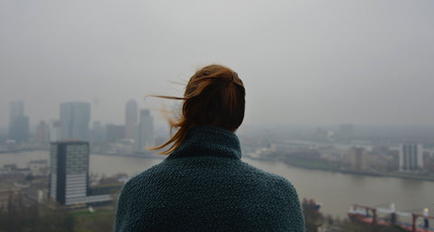 Woman starring on cloudy city.