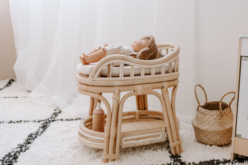 Tiny Harlow rattan doll's change table view from side with doll lying on the mattress with wooden bottle and rattan basket to the side