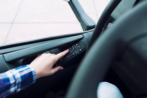 Photo of driver's hands pressing a button to roll the window up in a vehicle