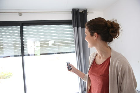 Photo of a woman using a remote control opens up blinds windows