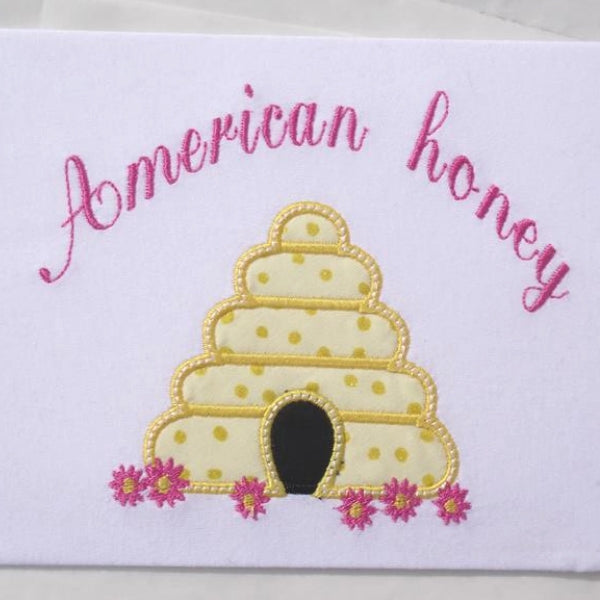 "An applique of a beehive with flowers and the words ""American honey"" embroidered above  by snugglepuppyapplique.com"