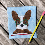 An applique of a French bulldog with his paws on a book and embroidered Glasses on this face by snugglepuppyapplique.com