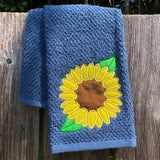 An applique of a sunflower with two leaves by snugglepuppyapplique.com