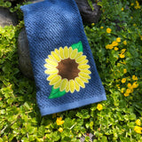An applique design of a sunflower with two leaves by snugglepuppyapplique.com