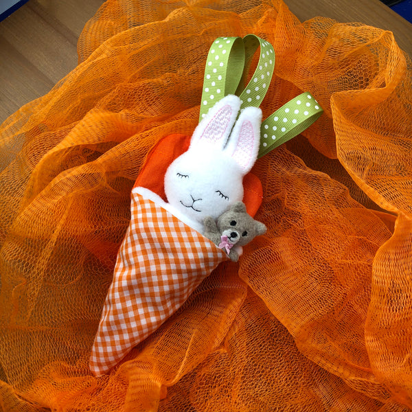 ITH bunny with teddy bear In a carrot bed with ribbon leaves embroidery machine design by snugglepuppyapplique.com