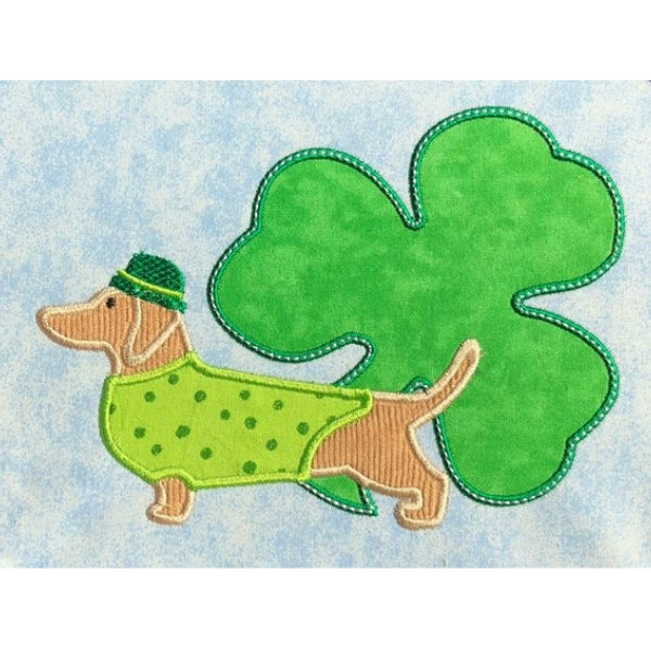 March Dachshund applique embroidery design, dog is wearing hat and coat with shamrock in the background, St. Patrick's day design