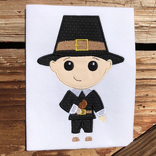 Pilgrim boy applique embroidery design, stylized with large head, holding a turkey drumstick with a bit taken out