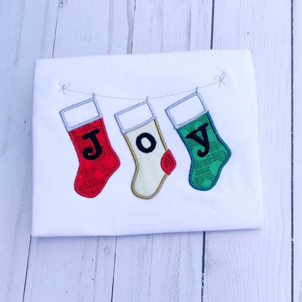 "An applique of three stockings hanging on a line with ""J O Y"" embroidered one letter on each  stocking by snugglepuppyapplique.com"