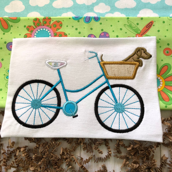 An applique of a bicycle with a basket and a dachshund inside the basket. snuggleppyapplique.com