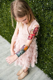 Little girl admiring her temporary tattoo sleeve from Tony Ray Tattoos with unicorns on it.